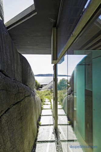 House with transparent walls on sunny rocky shores in Sandefjord, Norway